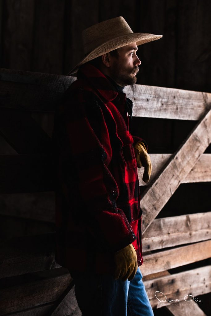 Cowboy standing in a dark barn